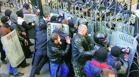 Pro-Russia protesters scuffle with the police in the regional government building in Donetsk on Sunday. (Reuters)