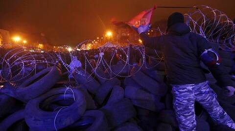 A Pro-Russian activist waves a Russian national flag atop of barricades at a regional administration building that they had seized earlier in Donetsk, Ukraine, Friday. (AP)