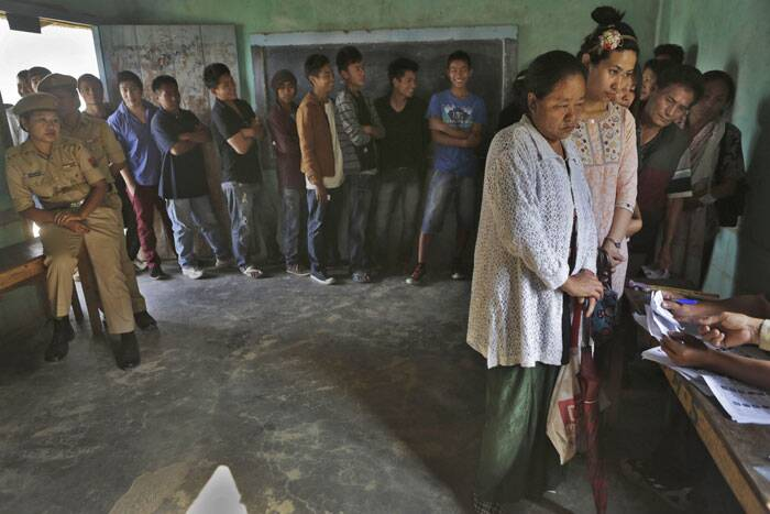 People stand in line to cast their votes inside a voting center at Senapati, in Manipur state. (AP)