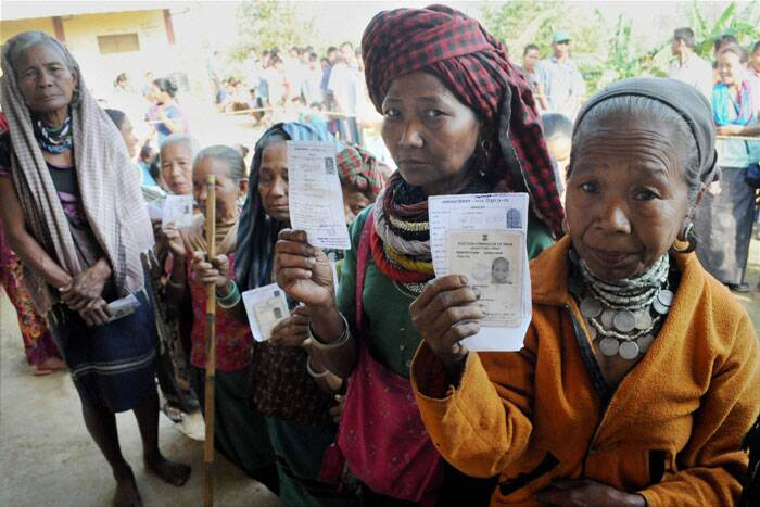 Woman voters show their voter identity cards as they wait in a queue to cast her vote for Tripura West Lok Sabha polls outside a polling station in Dhamcherra on Saturday. (PTI)