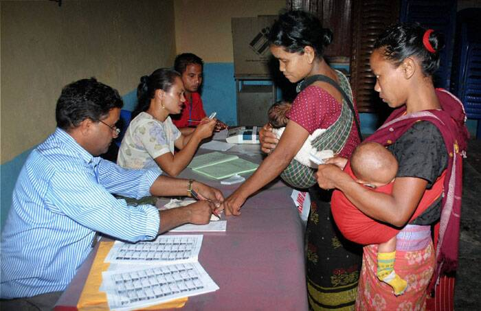 Security has been tightened in Khasi Jaintia Hills region following a 12-hr bandh called by banned HNLC since 5 am today. <br /> People get their ink mark as they queue to cast their vote at a polling booth at Ri Bhoi area, in Meghalaya on Wednesday. (PTI)