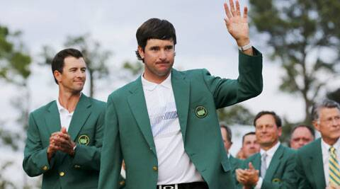 Bubba Watson waves with his green jacket in front of 2013 winner Adam Scott (L) after winning the Augusta Masters golf tournament at the Augusta National Golf Club in Augusta, Georgia.