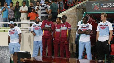 West Indies' captain Darren Sammy, standing third left, waits outside their team dug out with teammates and support staff after rain stopped play between Sri Lanka and West Indies (AP)