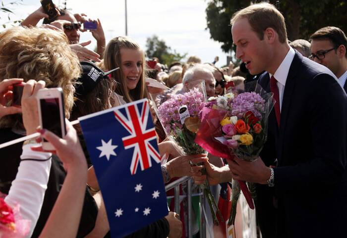 Prince William receives bouquet of flowers as he greets members of the crowd outside the Playford Civic Centre in the Adelaide suburb of Elizabeth. (Reuters)