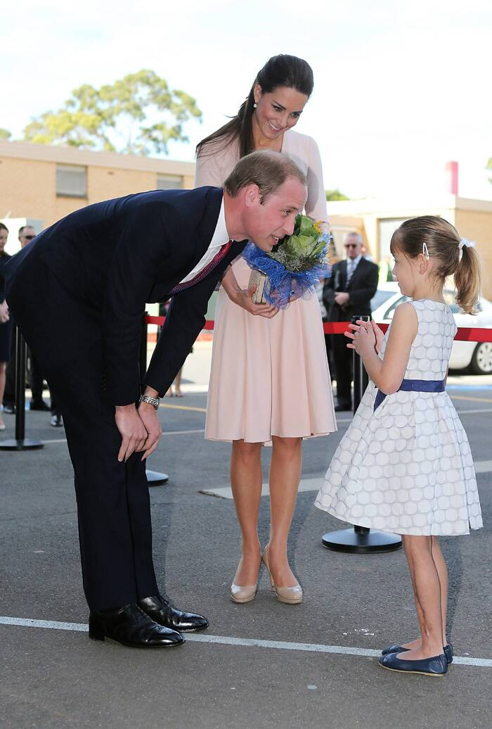 Prince William and Kate speak to a young girl at the youth community centre. (Reuters)
