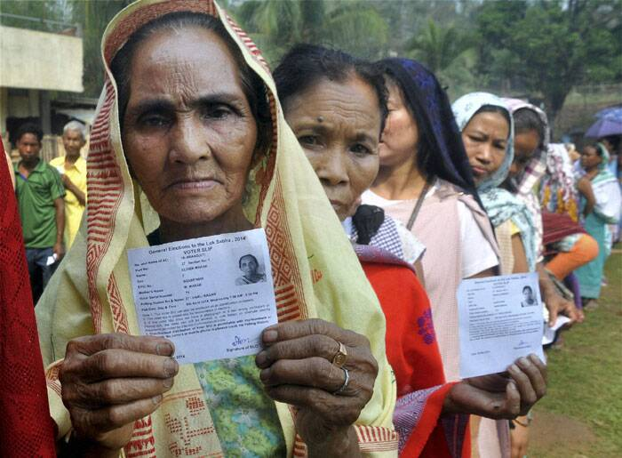 There are 343 sensitive polling booths out of 2,562, of which 85 per cent are in the militant-hit Garo Hills region and classified as hyper sensitive. Polling stations along the international border with Bangladesh and inter-state border with Assam are also classified as such. <br /> People show their voter identity card as they queue to cast their vote at a polling booth at Ri Bhoi area, in Meghalaya on Wednesday. (PTI)