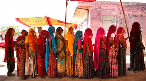 Women stand in a queue to cast their votes at a village near Sawai Madhopur, Rajasthan on Thursday. (AP)