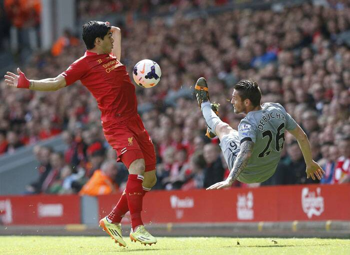 Liverpool's start player Luis Suarez (L) challenges Newcastle United's Mathieu Debuchy (R) during the  match. (Reuters)