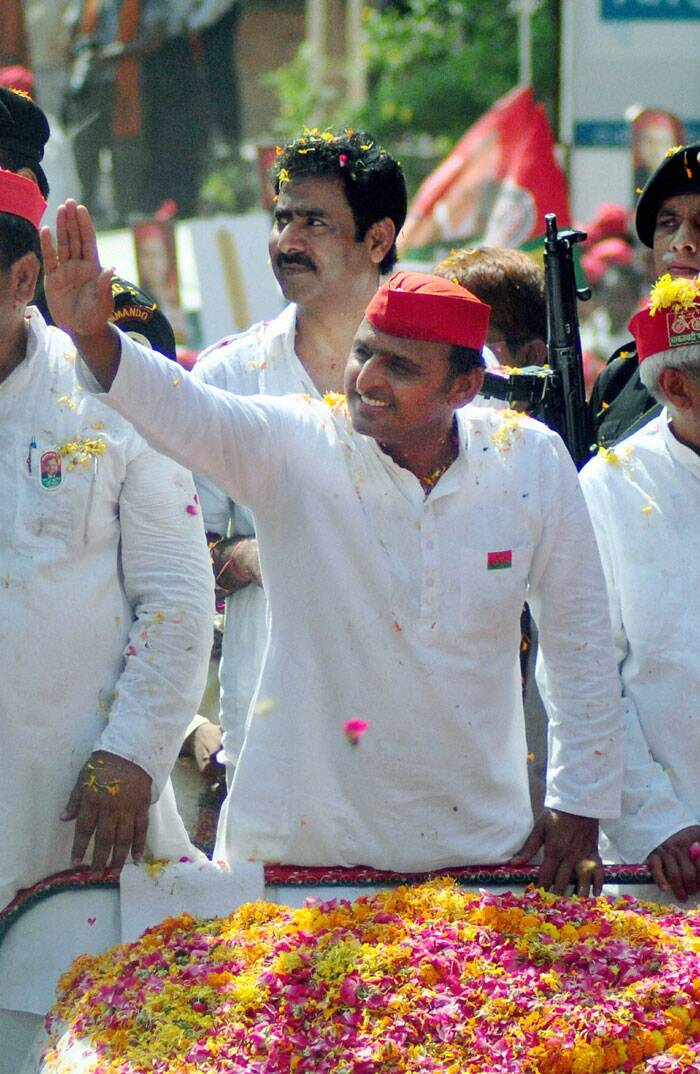 Uttar Pradesh Chief Minister Akhilesh Yadav waves to Samajwadi party supporters during an election campaign road show in Varanasi on Saturday. (PTI)
