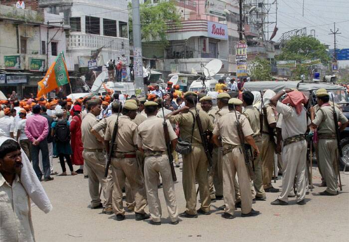 Policemen stand guard as BJP workers gather outside Banaras Hindu University to protest against Election Commission in Varanasi on Thursday. (PTI)