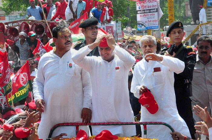 Uttar Pradesh Chief Minister Akhilesh Yadav with SP candidate Kailash Chaurasiya (L) during an election campaign road show in Varanasi on Saturday. (PTI)