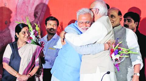 Senior BJP leader L K Advani hugs Narendra Modi as Rajnath Singh and Sushma Swaraj look on at the BJP head office in New Delhi, Saturday. Prem nath Pandey