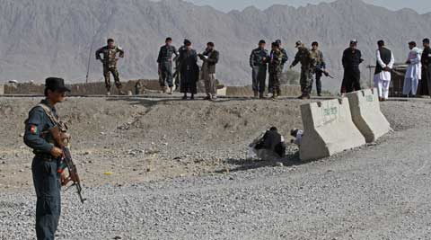 An Afghan policeman stands guard after a bomb explosion in Kandahar province south of Kabul, Afghanistan. (AP)