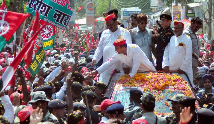 Uttar Pradesh Chief Minister Akhilesh Yadav shakes hands with Samajwadi party supporters during an election campaign road show in Varanasi on Saturday. (PTI)
