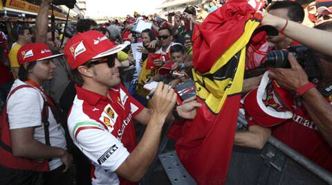 Ferrari driver Fernando Alonso of Spain signs autographs for fans at the Catalunya racetrack in Montmelo, near Barcelona, Spain (AP)