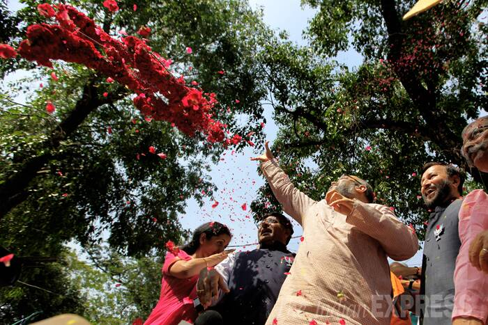 Amit Shah showers flower petals to celebrate his party's victory. (Source: Express Photo by Ravi Kanojia)