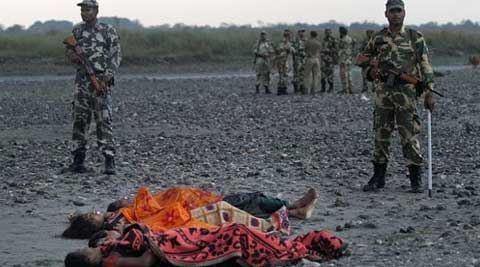 Bodies of victims killed in ethnic violence lie on the banks of the River Beki, as security officers stand guard at Khagrabari village, in Assam. (AP Photo)