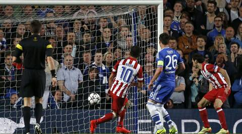 Atletico Madrid's Arda Turan (L) shoots and scores the third goal for the team during their Champions League semi-final match against Chelsea in London on Wednesday. (Reuters)