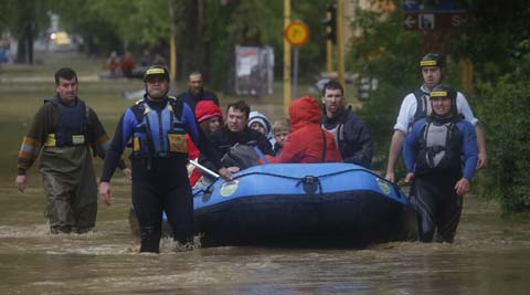 Members of the Bosnian Army rescue people from their flooded homes. (Source: AP)