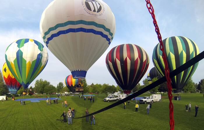 Balloons launch at 6:00 a.m., Friday through Sunday, at the Garrison Middle School field. The Night Glow is scheduled for Saturday at dusk, on the Walla Walla Community College campus. <br />Balloons are inflated during the Annual Balloon Stampede. (AP)