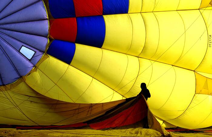 A helper stretches out part of a balloon as it is inflated during the media day launch  to prepare for the Annual Balloon Stampede. (AP)