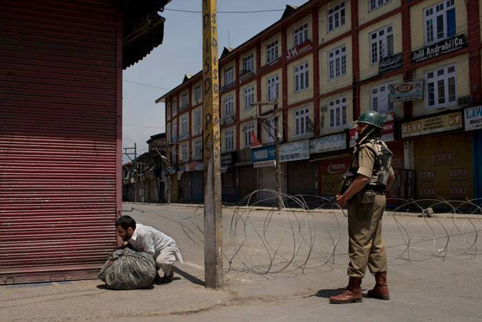 A Kashmiri man bends to get past a barbwire checkpoint in front a paramilitary soldier in Srinagar. <br /> The protests erupted in Nawa Kadal area in interior of the city when security forces were being withdrawn after poll duty. (AP)