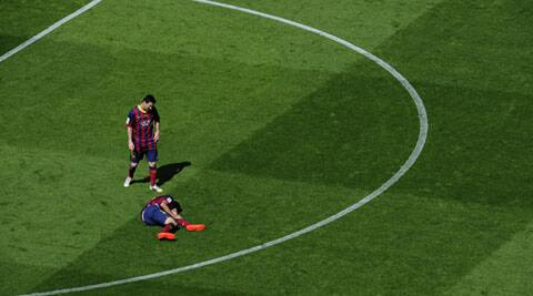 FC Barcelona's Lionel Messi, from Argentina, left, watches Sergio Busquets on the pitch during a Spanish La Liga soccer match against Getafe at the Camp Nou stadium in Barcelona (AP)