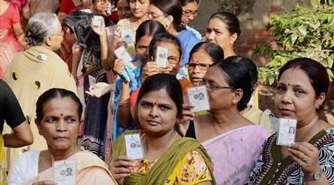Women voters displaying their voter ID cards while waiting to cast their votes at a polling booth in North 24 parganas in West Bengal on Monday. PTI photo