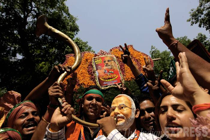 Men wearing Modi masks as they celebrate the party's victory. (Source: Express Photo by Ravi Kanojia)