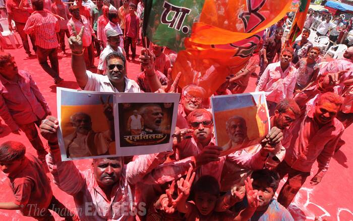 BJP supporters, smeared in gulaal, flash Modi-placards as they cheer for Narendra Modi in Pune. (Source: Express Photo by Sandeep Daundkar)
