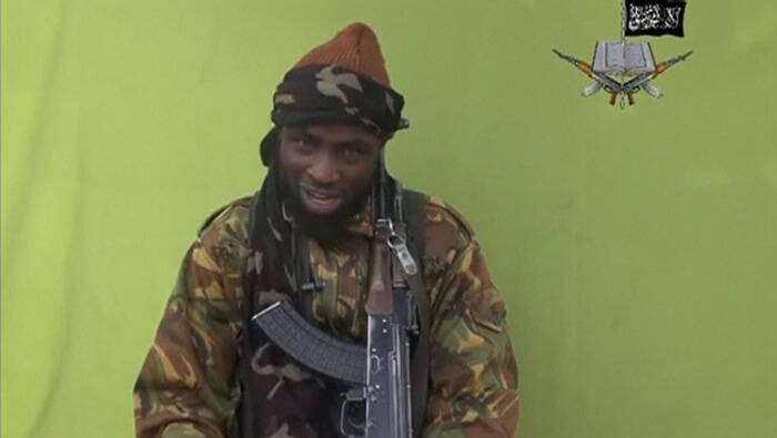 In a 1.25-minute segment of the YouTube video, scores of girls in black and grey veils sit on the ground, chant and sing. Shekau, wearing military fatigues and holding an AK-47, then addresses the camera. He appears confident and at one point even laughs. ( Source: Reuters )