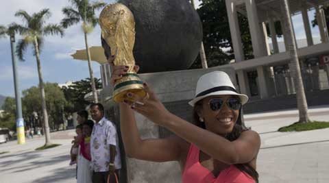 A tourist poses for a photo with a replica of the FIFA World Cup trophy outside Maracana stadium which will host World Cup matches in Rio de Janeiro, Brazil. (AP Photo)