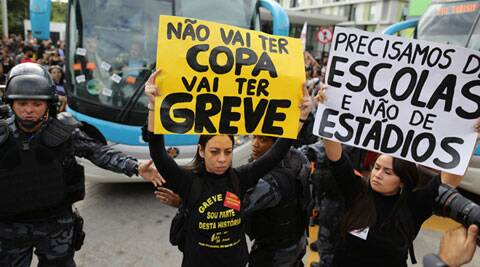 """Demonstrators hold up signs that read in Portuguese, """"There won't be a cup. There will be strikes, """"(left), and """"We need schools, not stadiums"""" as they walk in front of the bus carrying Brazil's national football team as it leaves a hotel for the Granja Comary Training Centre, where the team will train and reside during the World Cup, in Rio de Janeiro. (Source: AP)"""