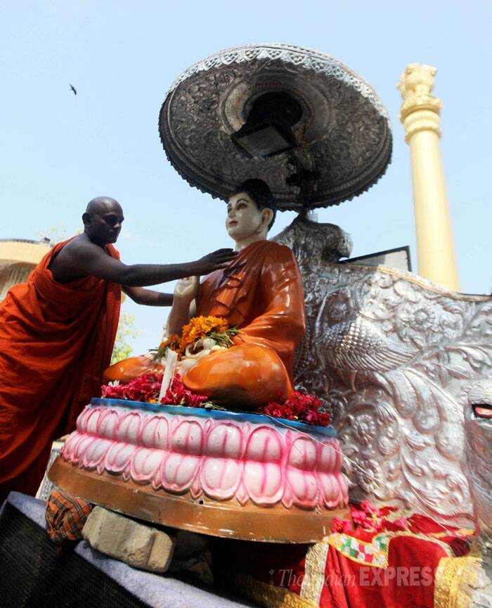 A Buddhist monk cleans the statue of Lord Buddha in Mumbai on Wednesday. (Source: Express photo by Prashant Nadkar)
