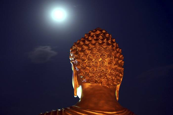 A full moon is seen behind a Buddha statue lit up on the eve of Buddha Jayanti festival at a monastery in Bhopal. (Source: AP)