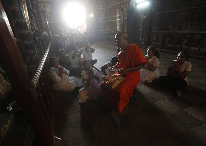 A Buddhist monk blesses devotees on Buddha Jayanti at Kelaniya temple in Colombo. (Source: Reuters)