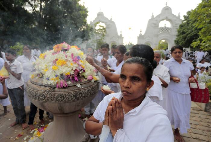 A Buddhist devotee prays during religious observances on Buddha Purnima in Colombo. (Source: AP)