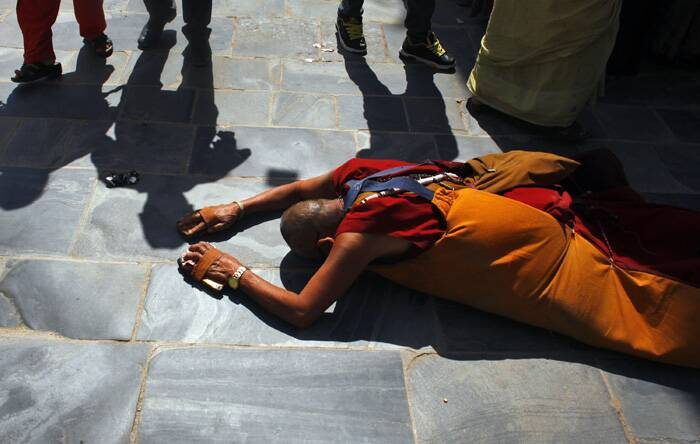 A Buddhist monk prostrates and circumambulates the world heritage site Boudhanath Stupa during Buddha Jayanti in Katmandu. (Source: AP)
