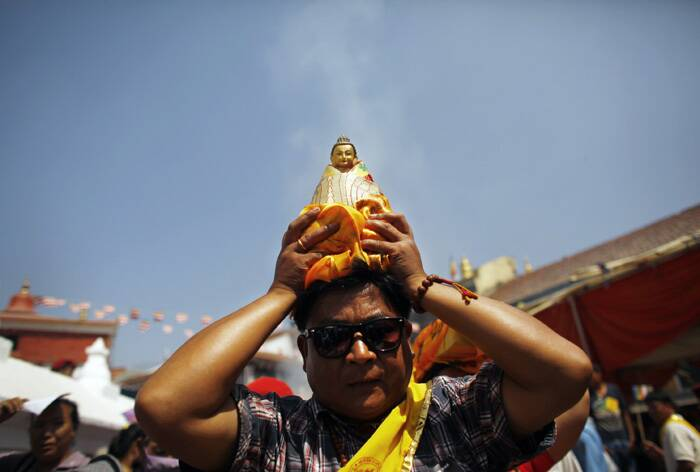 Devotees around the world are celebrating Buddha Jayanti or Buddha Purnima, an annual celebration of Buddha's birth, enlightenment and death.<br />A devotee carries a statue of Buddha and circumambulates the world heritage site Boudhanath Stupa during Buddha Jayanti in Katmandu, Nepal. (AP)