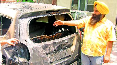 Complainant with the burnt car outside the police station in Phase 1, Mohali.