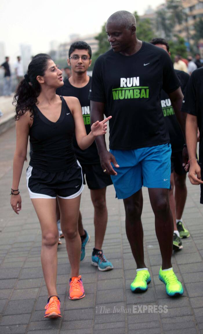 Carl Lewis interacts with a young runner. (Source: Express photo by Kevin Dsouza)