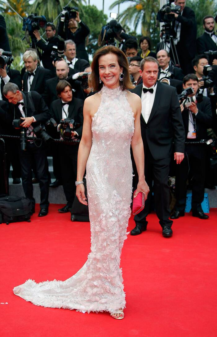 Jury Member Carole Bouquet was elegant in a silvery white down with a red clutch. <br /><br /> The actress smiles as she arrives for the opening ceremony of the 67th Cannes Film Festival and the screening of the 'Grace of Monaco'. (Source: Reuters)
