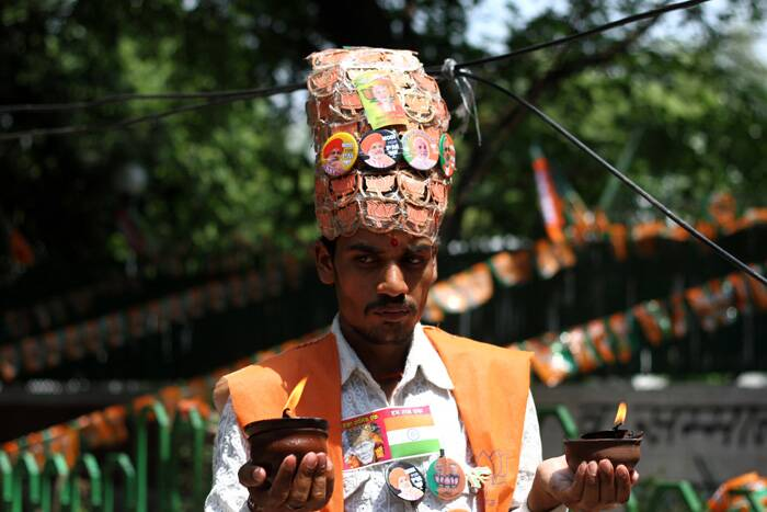 A BJP supporters wears a hat with Modi-buttons to celebrate Modi's victory in Lok Sabha elections at BJP headquarters, in New Delhi. (Source: Express photo by Ravi Kanojia)