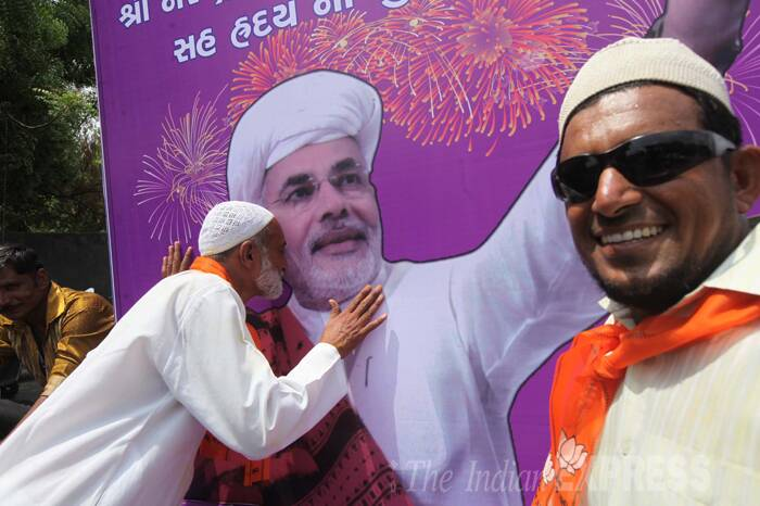 Ecstatic party member kissed Modi's poster. (Source: Express Photo by Bhupendra Rana)