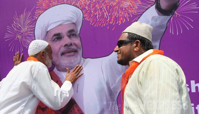 A Muslim man kissing a poster of BJP's Prime Ministerial candidate Narendra Modi. (Source: Express Photo by Bhupendra Rana)
