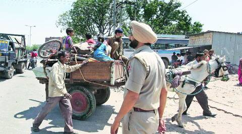 GMADA staff and Punjab Police officers stop slum dwellers from entering Mohali on Saturday. Jasbir Malhi