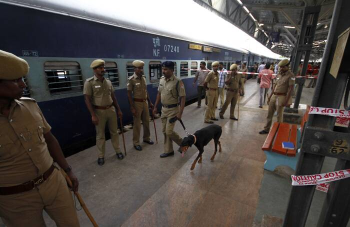 Policemen stand guard next to a passenger train that was ripped by two blasts at the railway station in Chennai. (AP)