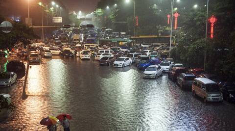 In this photo taken Sunday, May 11, 2014, residents wade through a flooded street in Shenzhen in southern China's Guangdong province. (AP)