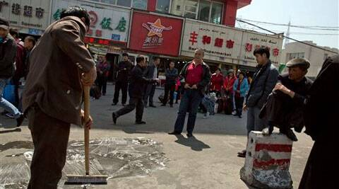 People watch a man wash and scrub the site of an explosion outside the Urumqi South Railway Station in Urumqi, northwest China's Xinjiang Uygur Autonomous Region.  (Source: AP)