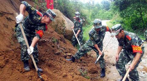 In this photo released by China's Xinhua news agency, rescuers try to clear off a road after a major earthquake, at Wupai Village of Kachang Township in Yingjiang County, southwest China's Yunnan Province, Friday, May 30, 2014.